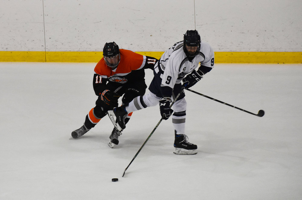 Junior defender Tanner Salsberry fends off an opponent in the team's game against Buffalo State on Saturday Nov. 3. The game ended in a 4-4 tie after three full periods of play and five minutes of overtime (Josie Kwan/assoc. photo editor).