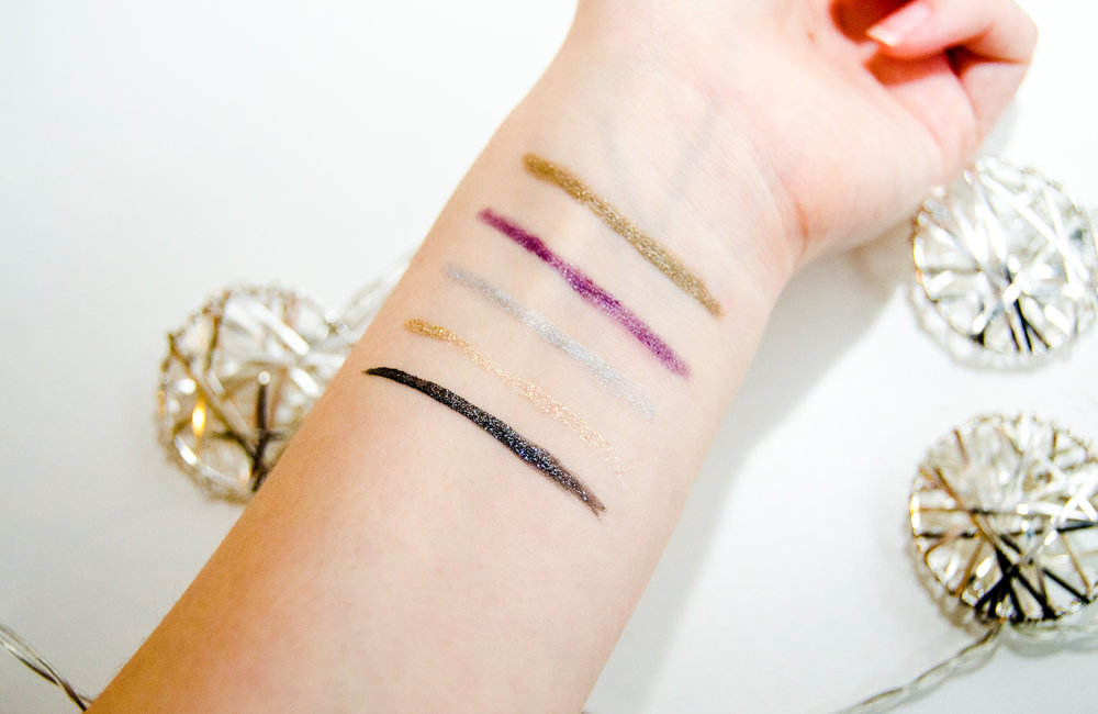 Swatches of my metallic eyeliners. From top to bottom: Starlooks Gem Eye Pencil in Ultra Olive, Starlooks Gem Eye Pencil in Ultra Orchid, Mally Beauty Evercolor Starlight Waterproof Liner in Starshine, NYX Liquid Crystal Liner in Crystal Silk, NYX Liquid Crystal Liner in Crystal Onyx