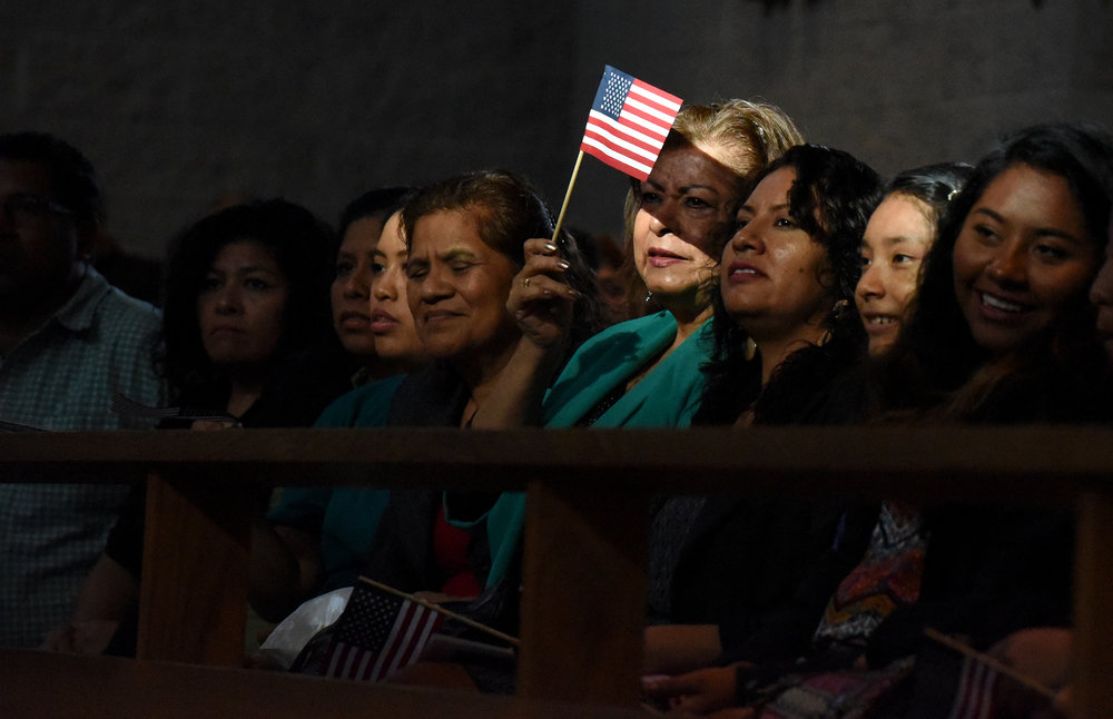 Lucia Orozco-Mireles, blocks the sun out of her eyes with an American flag while she listens to speakers at the Immaculate Conception Catholic Church in Durham, on October 30, 2016. More than 1,000 members of the North Carolina Congress of Latino Organizations met with North Carolina candidates for governor and U.S. senate during a public nonpartisan meeting.