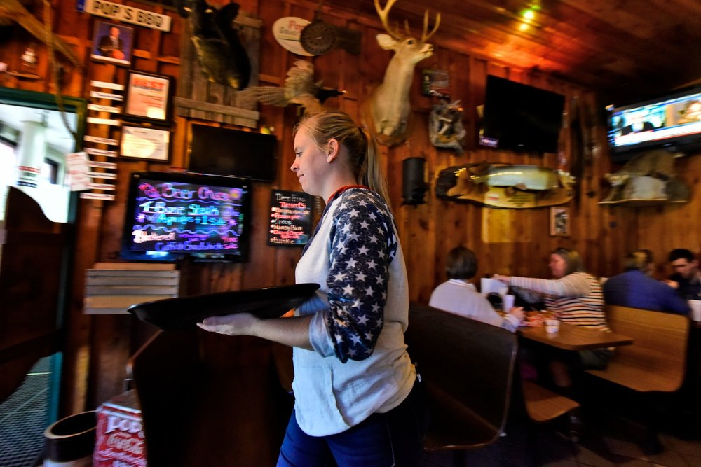 Jessie Crawford, 27, waits tables at Pop's BBQ, a southern style barbecue restaurant that draws a crowd of tourists and locals seven days a week.