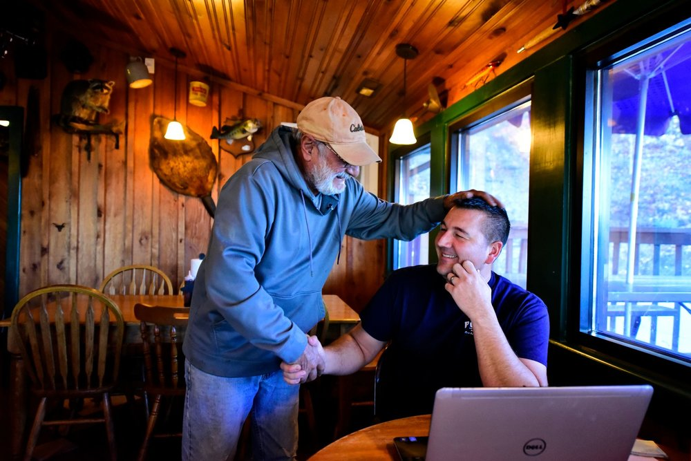 "Mike Winer, left, a Pop's BBQ regular, greets Adam. Adam fosters the values of community and family at Pop's. ""Sometimes he comes in for five minutes to talk, sometimes it's 30 minutes,"" says Adam."