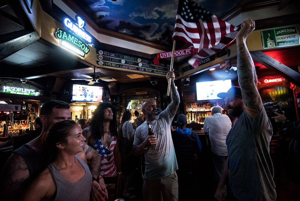 Kristin Henry (front/left), Paddy McGrave (back/left), and Jeff Egyp, react to George (center) and Andy Guiles flying the American Flag inside Slainte Irish Pub. is one of two bars open for business despite the expected landfall of Hurricane Florence in Wilmington, NC, USA, September 13, 2018.