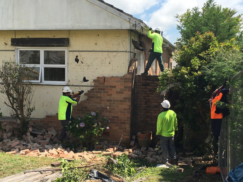 Our crew in action, removing the brick facade to expose the asbestos fibre boards.