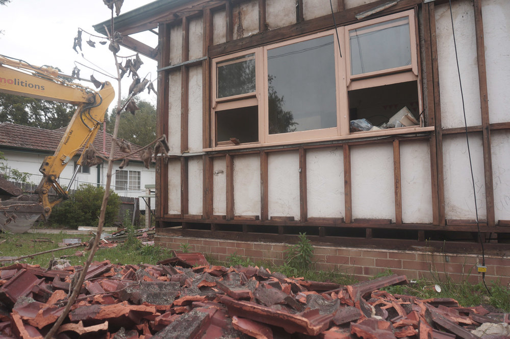 House stripped of asbestos, ready for structural demolition to begin.