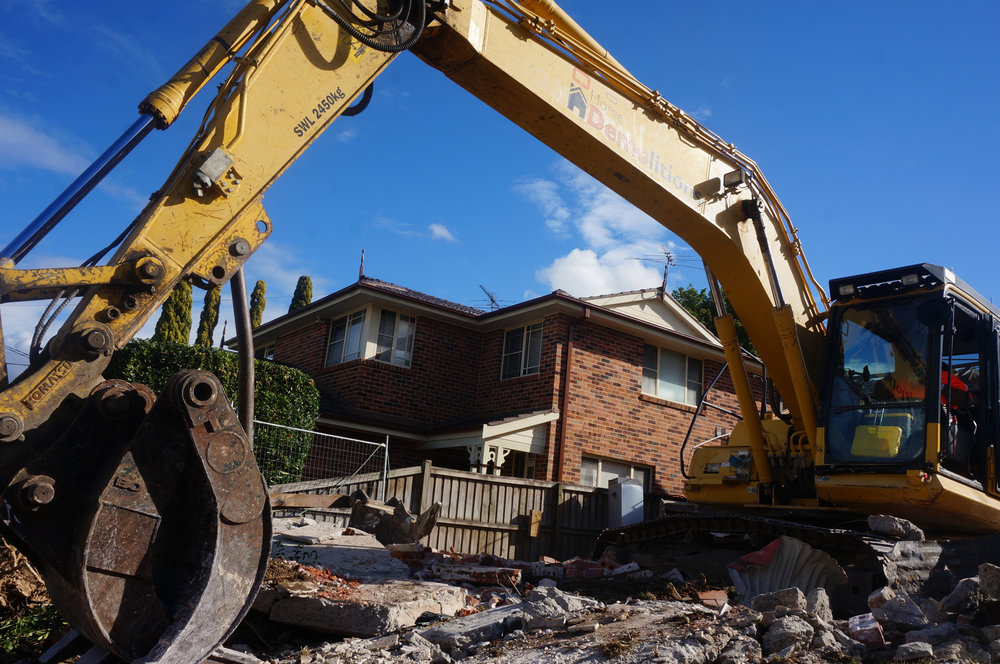 Excavator amongst cracked cement at demolition site in West Ryde.jpg
