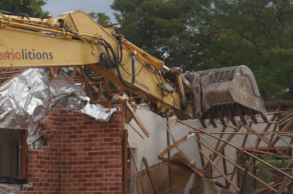 Excavator demolishing roof support beams in West Ryde.jpg