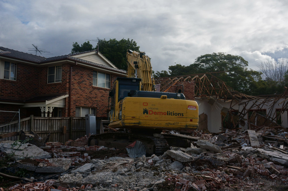 Excavator halfway through demolition of house in West Ryde.jpg