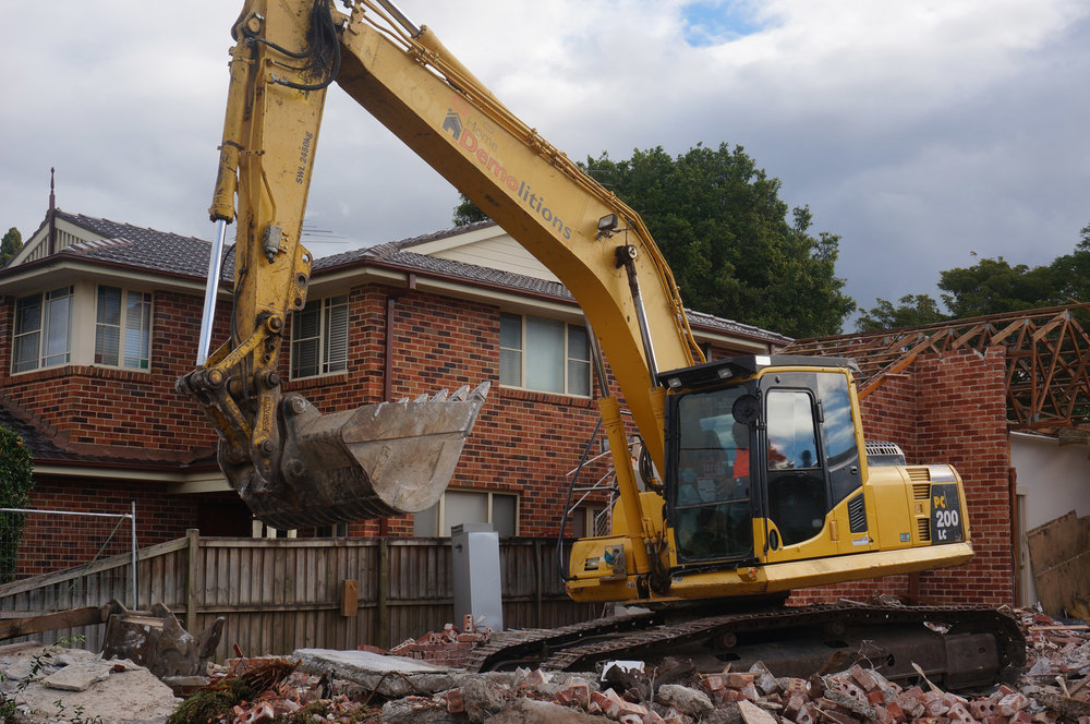 Excavator in front of partially demolish brick home in West Ryde.jpg