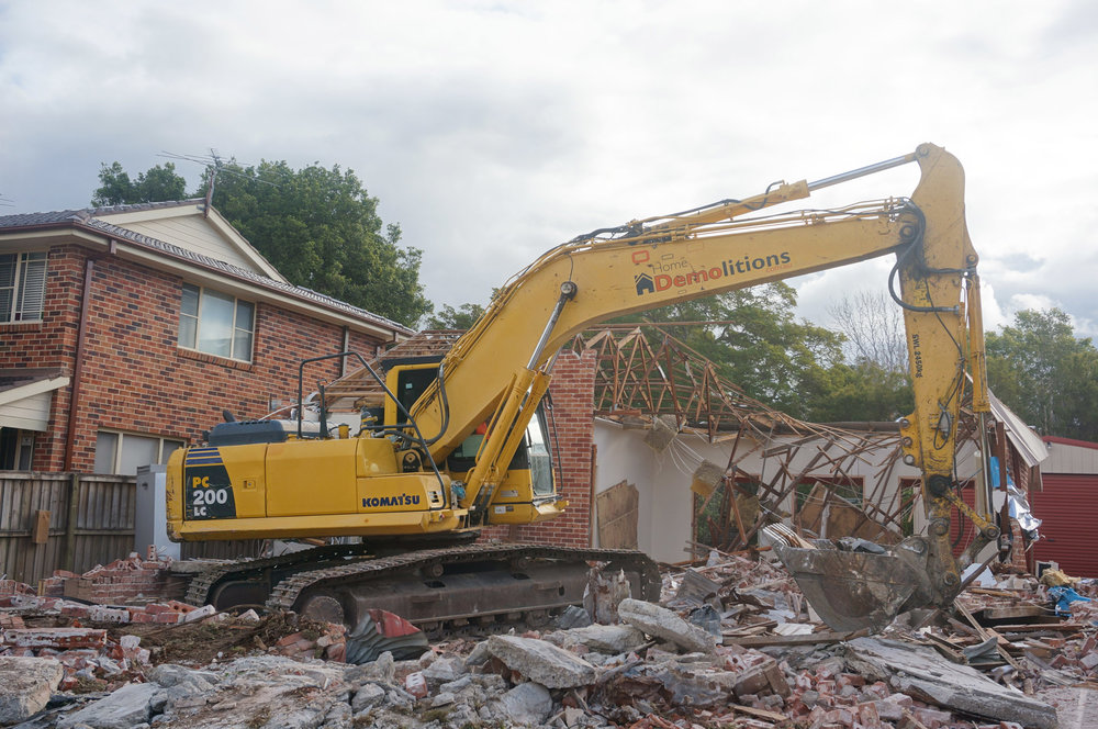 Excavator with bucket attachment clearing debris at demolition site in West Ryde.jpg
