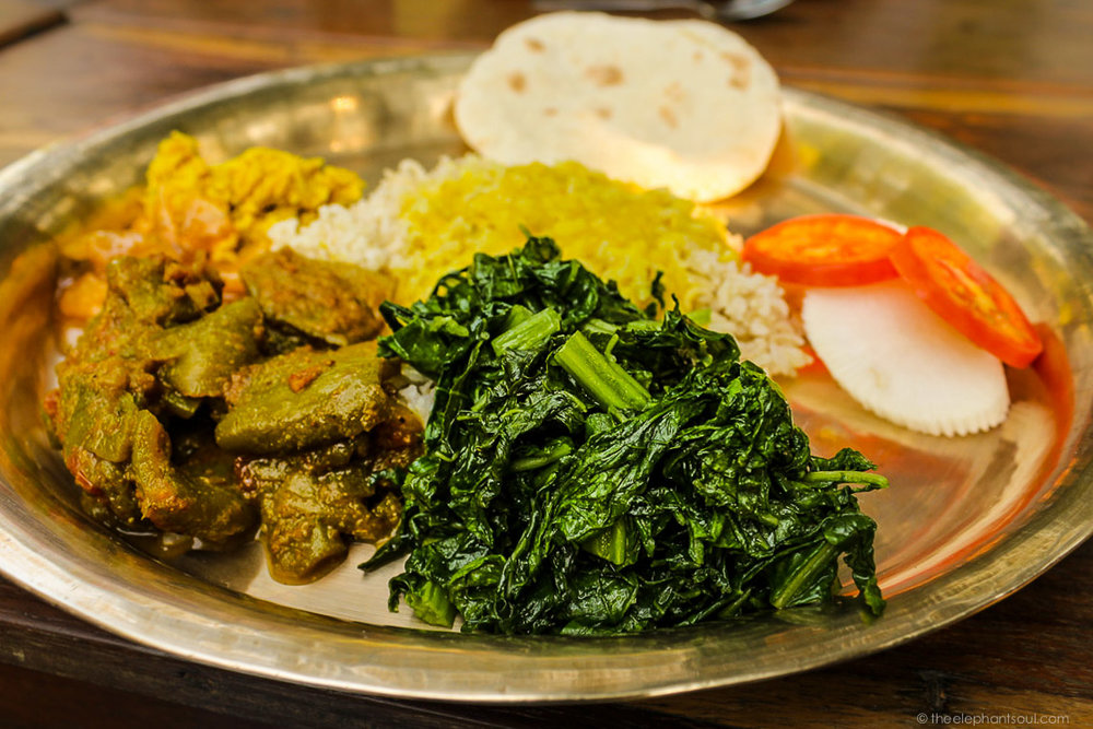 This delicious Nepali dhal bhat and tarkari (lentil, rice and vegetables) is an everyday meal in Nepal. It's usually vegan, if not cooked with ghee. Photo taken during my trip to Tiger Tops Elephant Camp in Chitwan, Nepal.