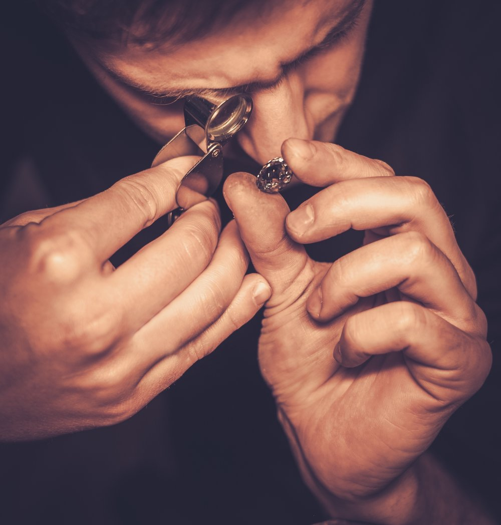Jeweler studying a cremation diamond under a loop