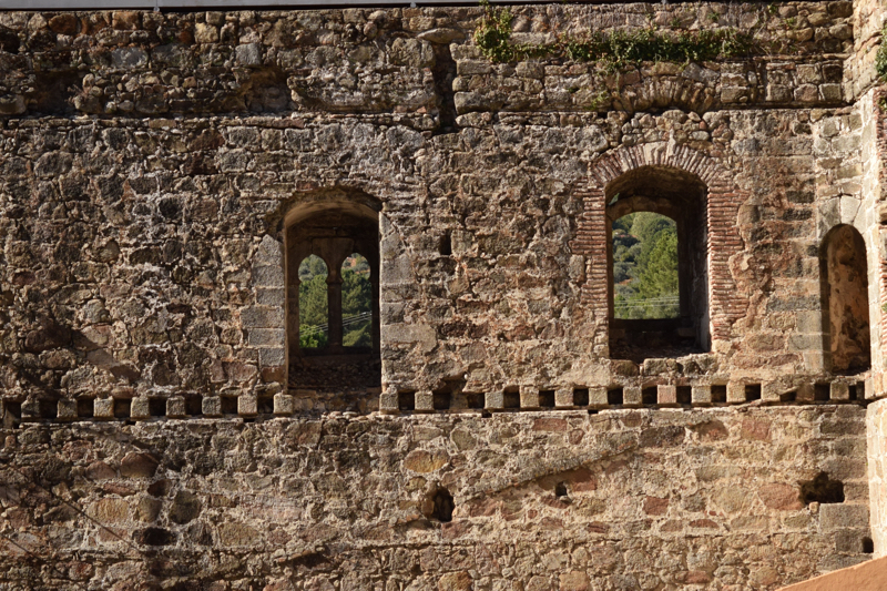 Different style of windows on the same wall of the castle Arena of San Pedro