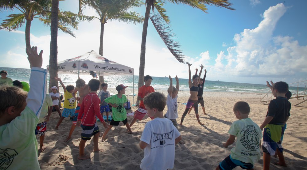 Our Surf Camps in Fort Lauderdale Beach provide a safe, fun and educational introduction to surfing and the ocean environment for children age 5 and up. Our low ratio of 1 instructor to a max of 7 students guarantees safety and quick results. Personal dedicated attention and, most importantly, safety is our mission. All our Instructors are CPR & First-Aid Certified and are among the top surfers and watermen in the area, each with years of training and teaching experience. We guarantee your kids will be surfing by the end of the first week!   Below are the topics we will be working on during each camp week:   - Standing up  - Paddling  - Wave timing/placement  - Wave selection  - Surfboard and wet suit education  - Wave physics  - Surf etiquette and safety