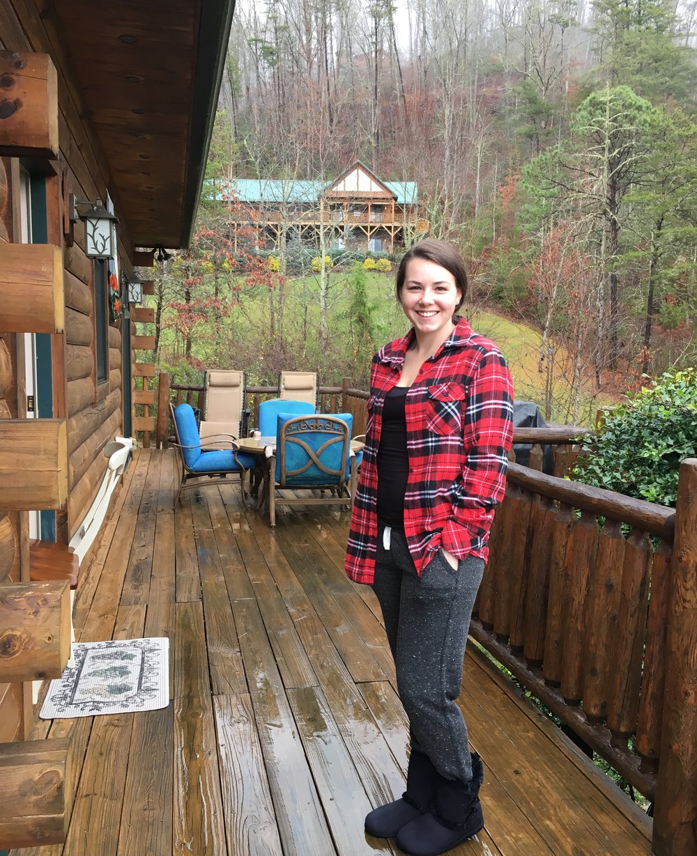 in my new flannel and slippers standing on our cabins wrap around porch.