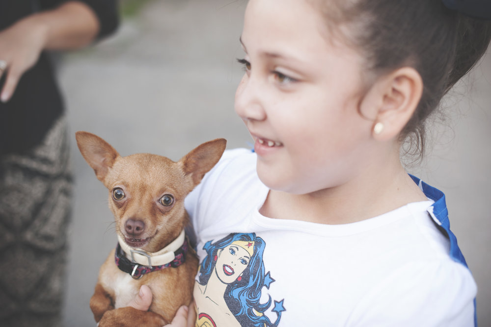 Girl holding her beloved chihuahua, who peacelovedogs offered to pay to spay.