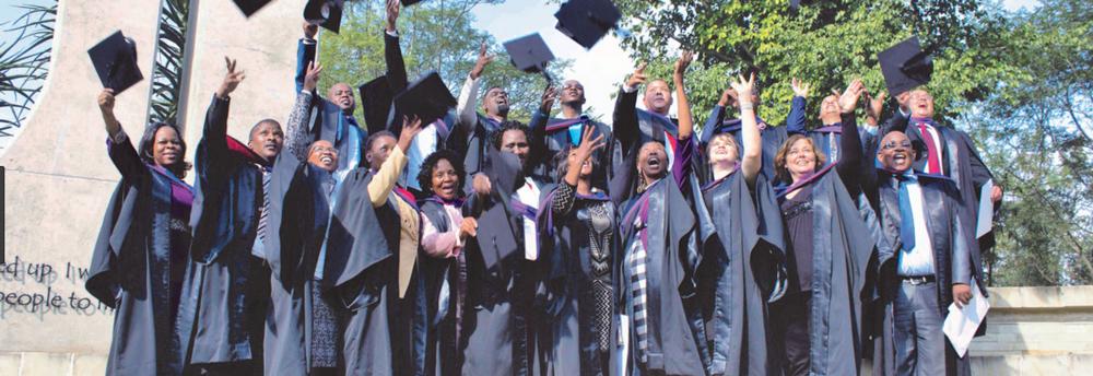 Graduates of Seth Mokitimi Methodist Seminary celebrate in the school courtyard.
