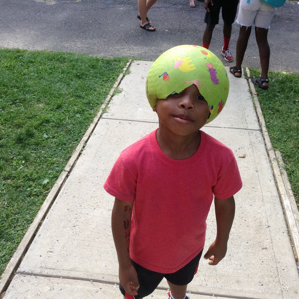 child with pink t-shirt and soccer ball on his head