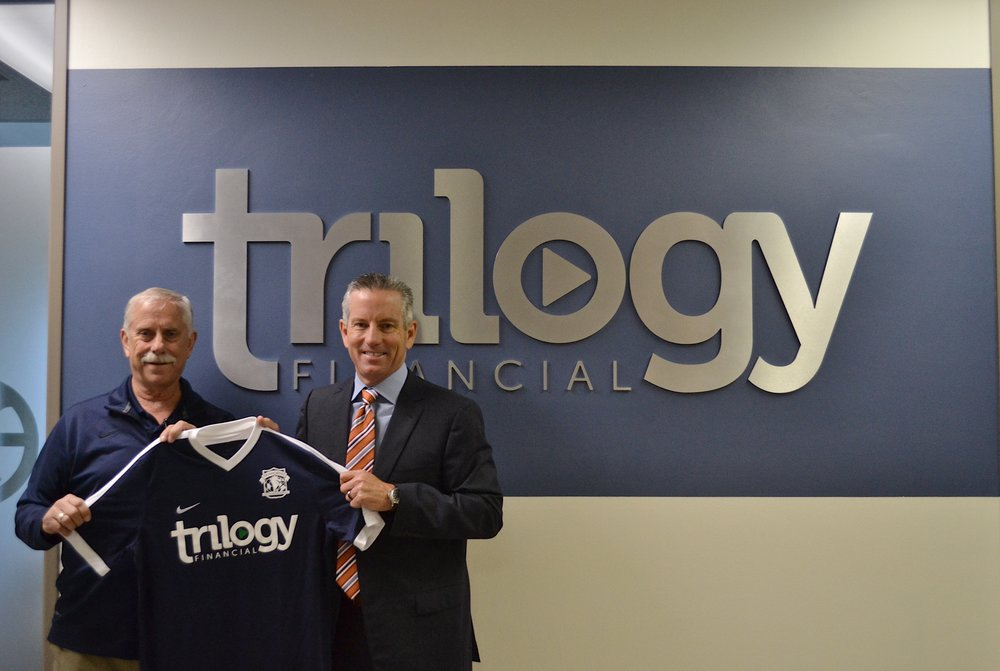 PDL GM, Mark Schrock, stands with President of Trilogy Financial, Jeff Motske, while holding the new away jersey with Trilogy sponsorship.