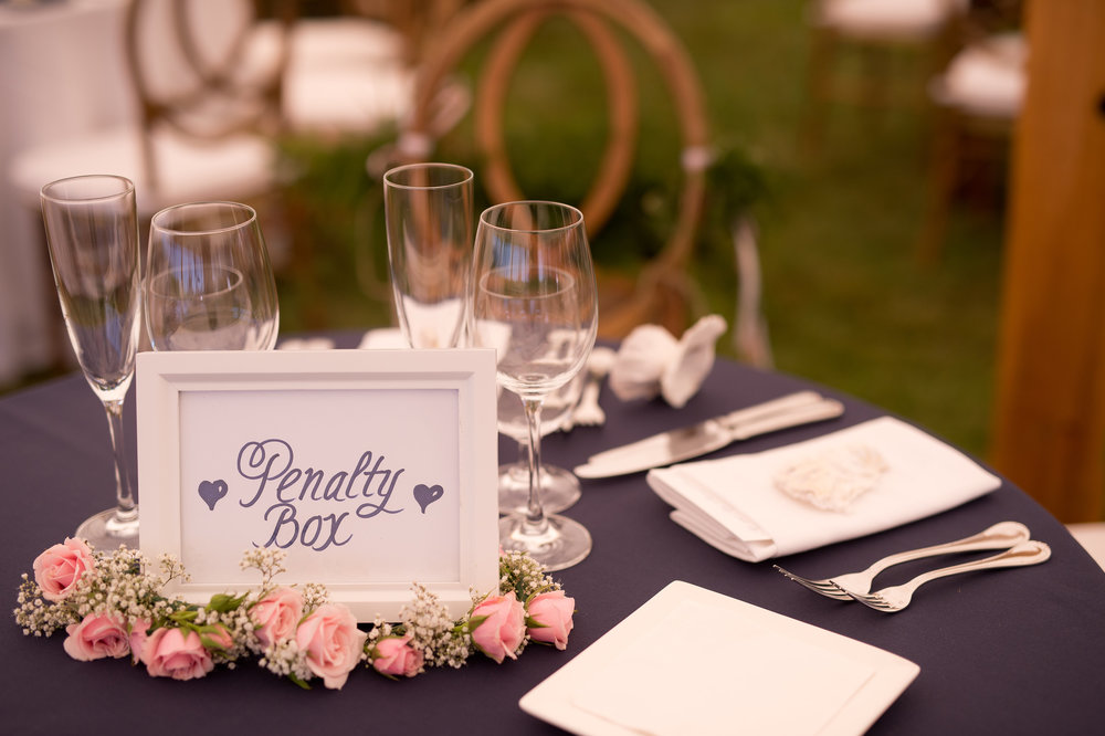 "As avid hockey fans, the bride and groom named tables after NHL teams. The sweetheart table was dubbed the ""Penalty Box"" and hockey sticks were signed in lieu of a guest book."