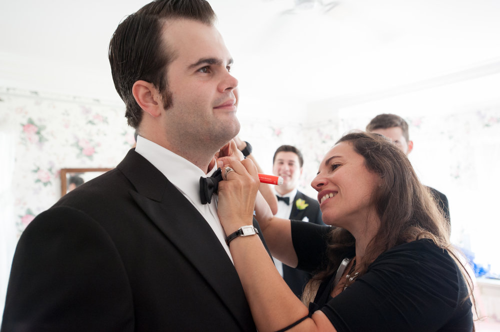 Making sure the groom's collar is in tip-top shape before he walks down the aisle.