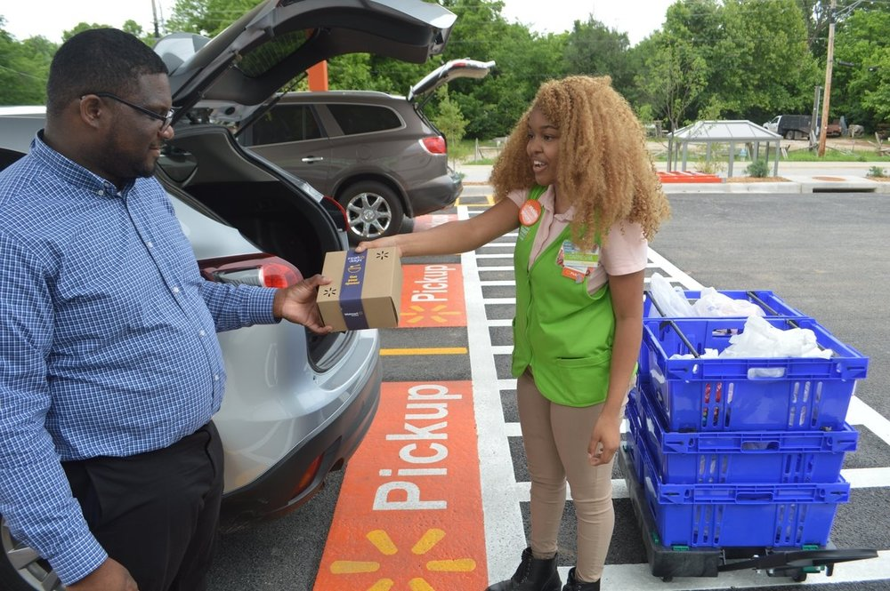 Walmart associate Mesha Davis and John Calloway, a field e-commerce market coach for Walmart, demonstrate how customers are able to pickup groceries at a new Walmart Neighborhood Market in Fayetteville.