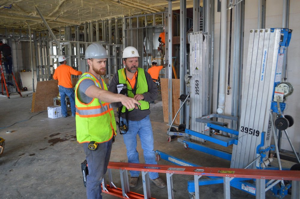 Cory Meyer of Modus Studio, the firm that designed Uptown Fayetteville Apartments + Shops, talks with a worker at the construction site.