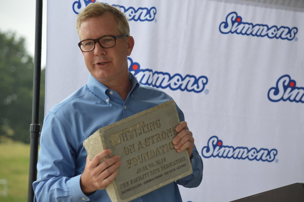 Todd Simmons, the CEO and vice chairman of Simmons Foods, holds one of the commemorative blocks that will be given to Benton County and the cities of Decatur and Gentry to show the company's commitment to building a strong foundation in each of the communities.