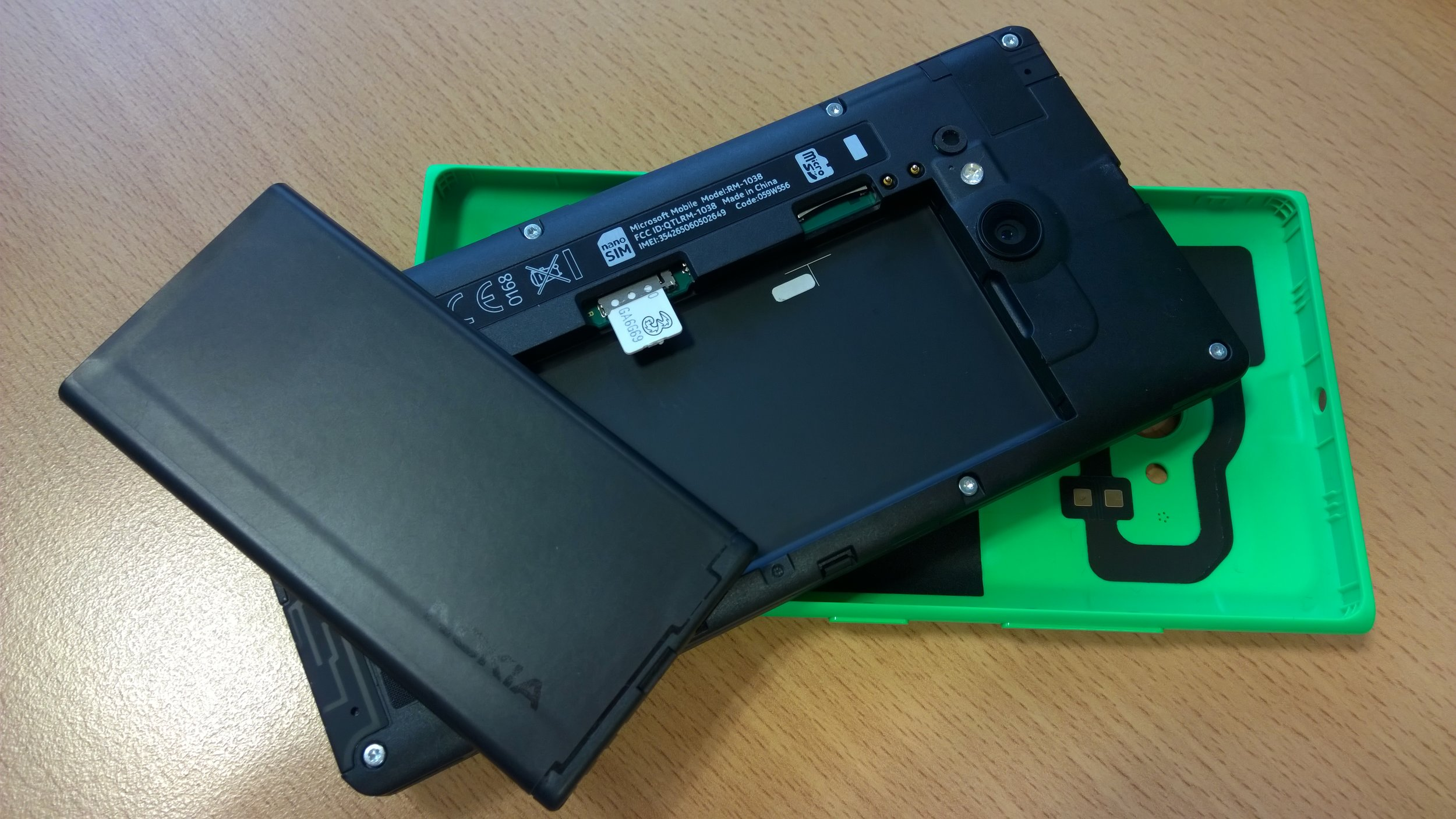 Battery and cover removed, showing SD and SIM slots, and wireless charging inside the case.