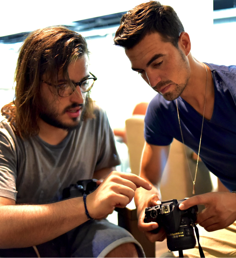 One of the photography teachers, Stergios, points out some focusing tricks on the camera equipment to a student during an indoors photo class session.