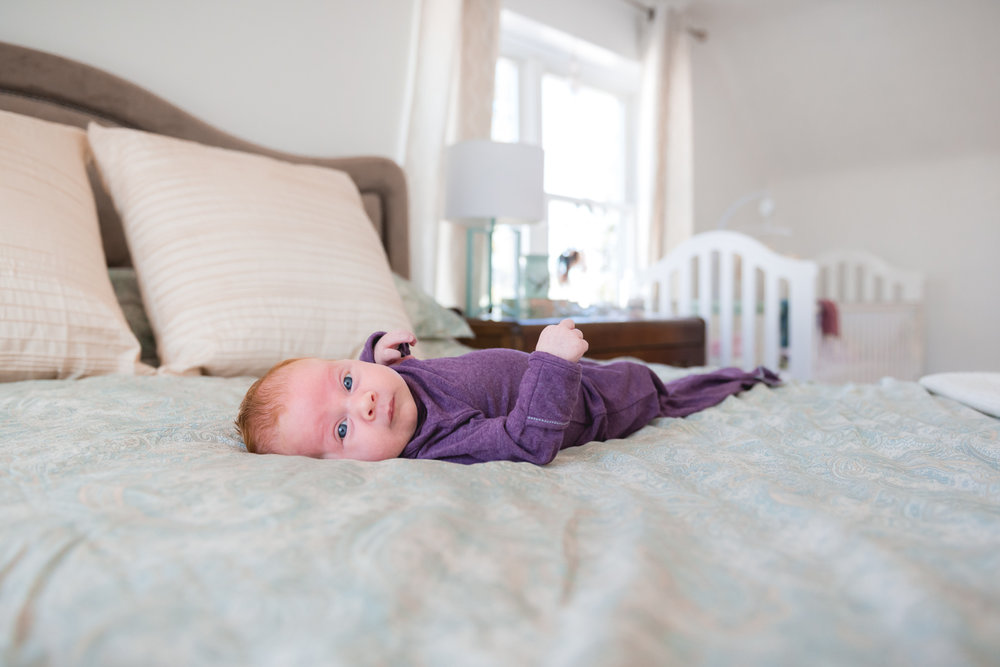 Baby on bed in purple sleeper during lifestyle session