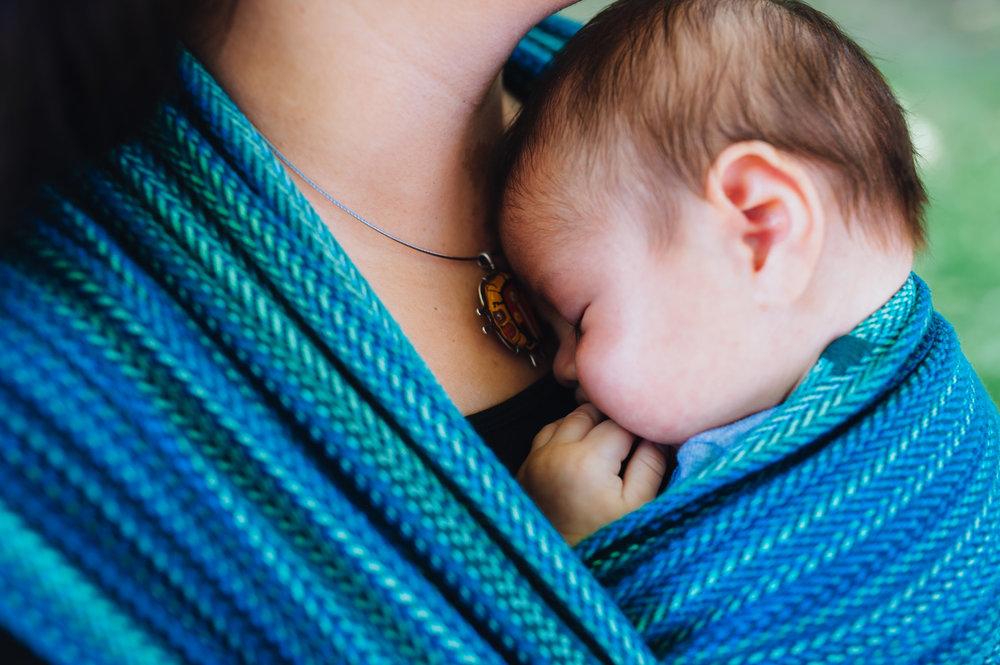 Newborn baby cuddling Mom in blue Seawater Wrap