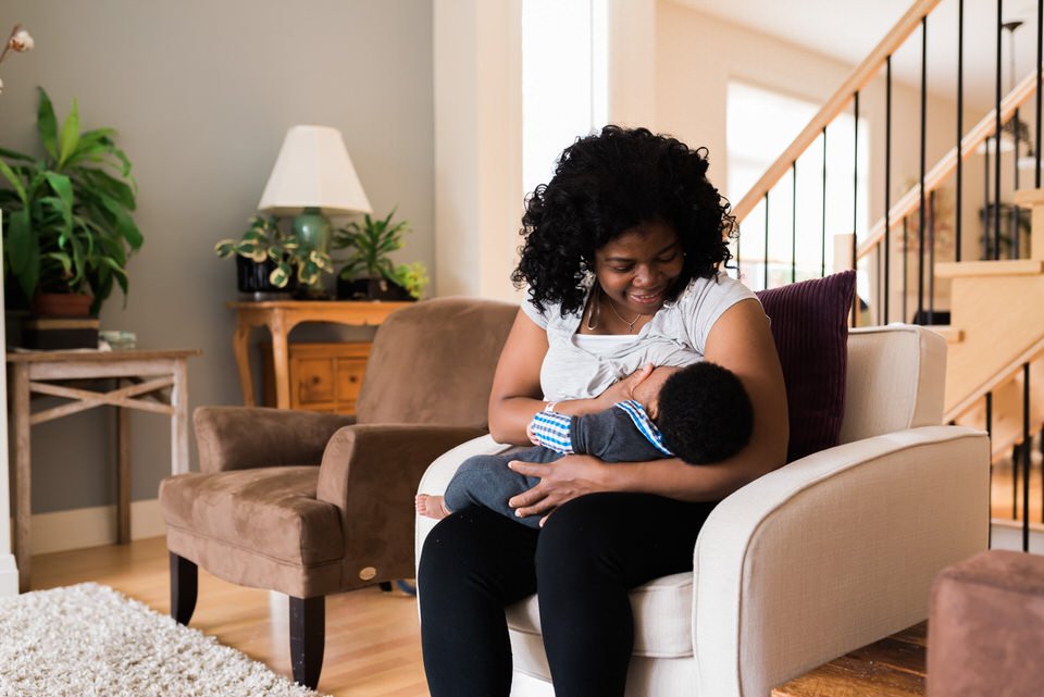 Mom gazes at baby boy while he breastfeeds at home photography session