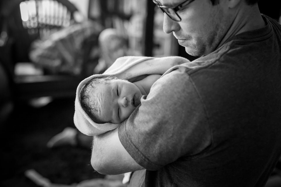 Infant in Dad's arms after home birth with Ottawa Midwives