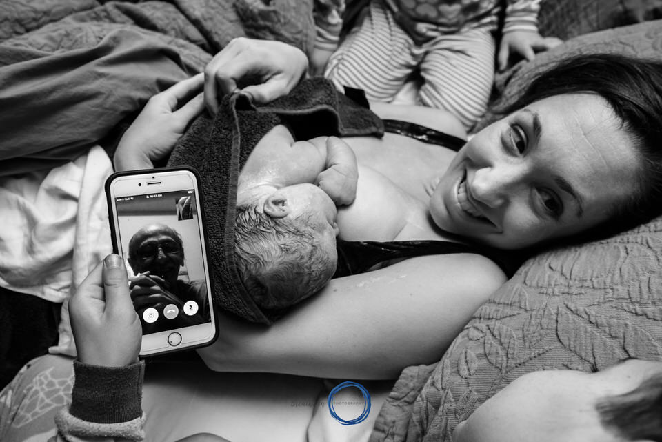 Using Facetime to meet your grandchildren.  Mom smiling at son with newborn baby on her chest.
