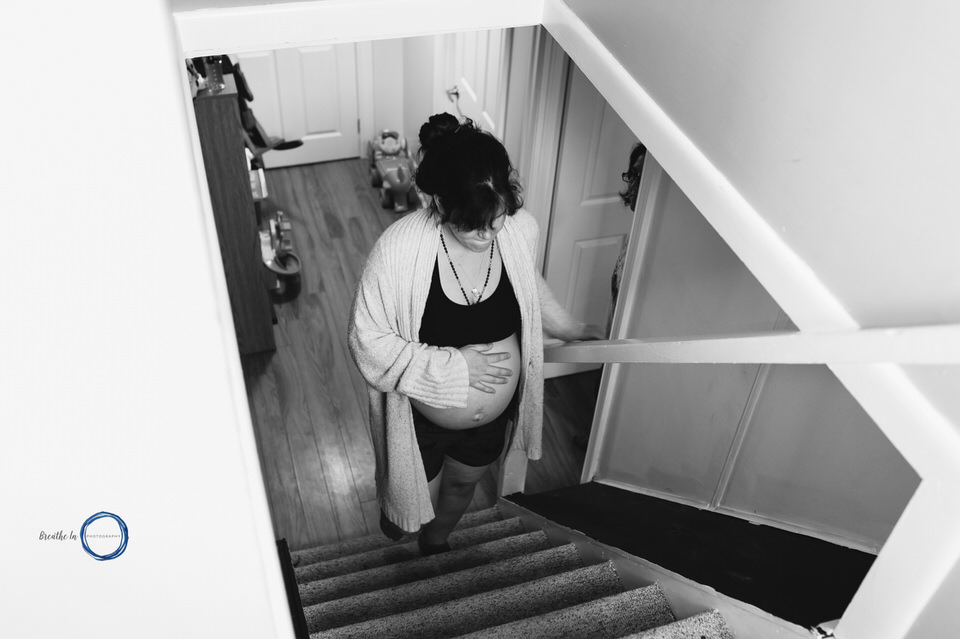 Woman in labour climbing stairs to keep things moving during Ottawa Home birth with Midwives.