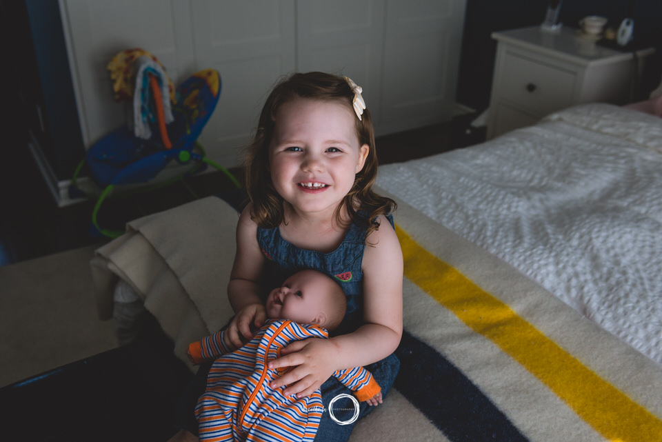 Big sister with doll on bed during lifestyle session in Ottawa