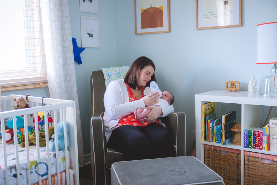 Mom bottle feeding baby in rocking chair in beautiful nursery.