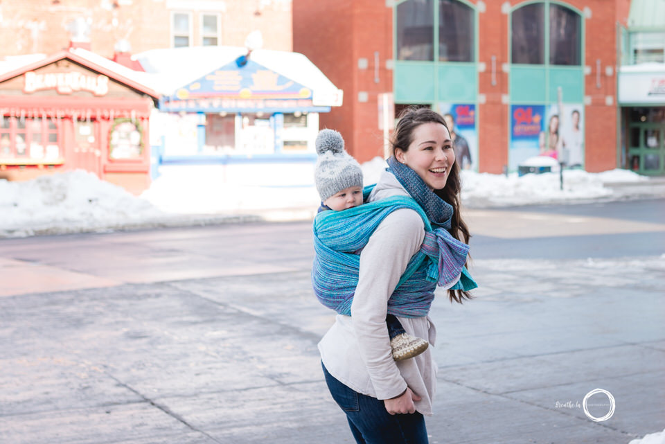 Babywearing Mom in Market with son on sunny day in blue wrap.