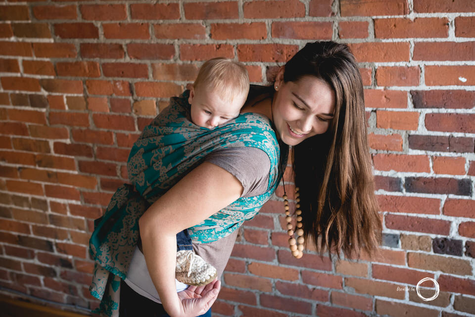 Mom smiling with baby boy on her back while babywearing in green wrap.