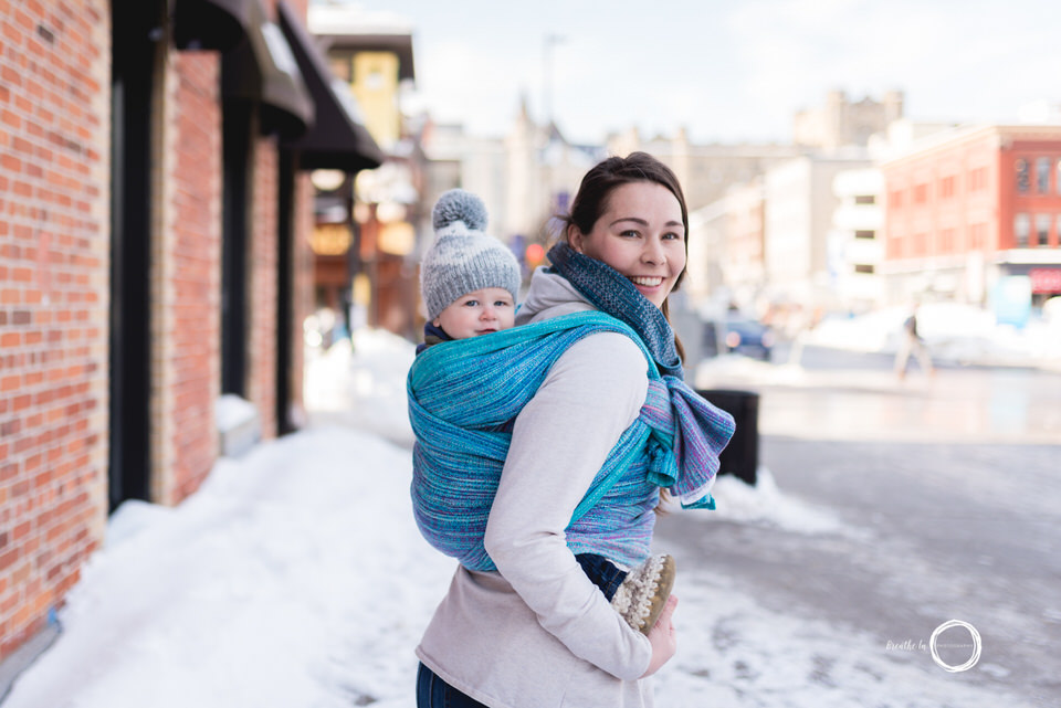 Mom carrying her son on her back in beautiful blue Zatgebo Adelfia silk wrap in market.