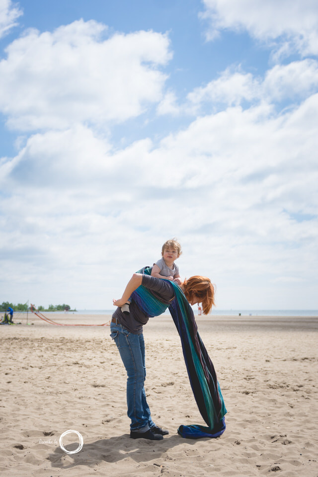 Mom putting baby on her back in woven wrap during babywearing photos session on the beach.