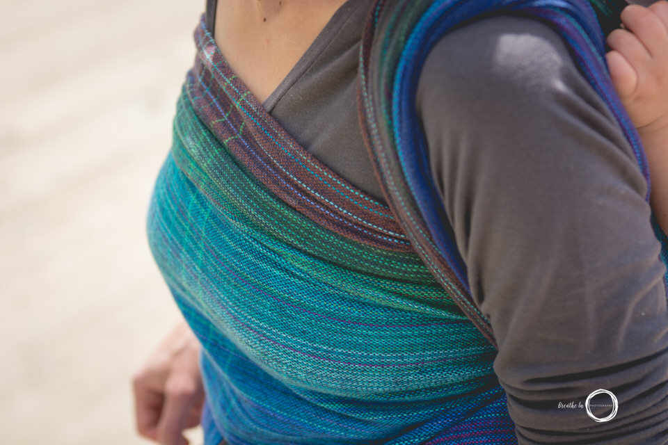 Details of beautiful handwoven babywearing wrap on beach.