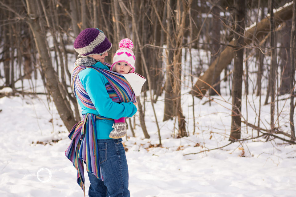 Mom carries daughter in Storch Inka wrap in the snow at Vanier Sugar Bush.