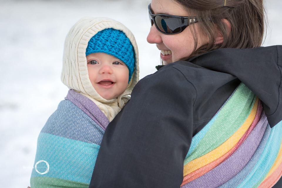 Mom babywearing son in Girasol Snow Rainbow Wrap.