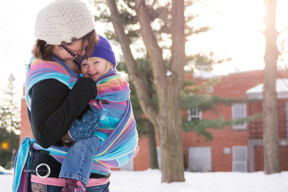 Mom carrying daughter in Metamorphosis Conversion with Girasol Rainbow Wrap at Vanier Library in the winter.