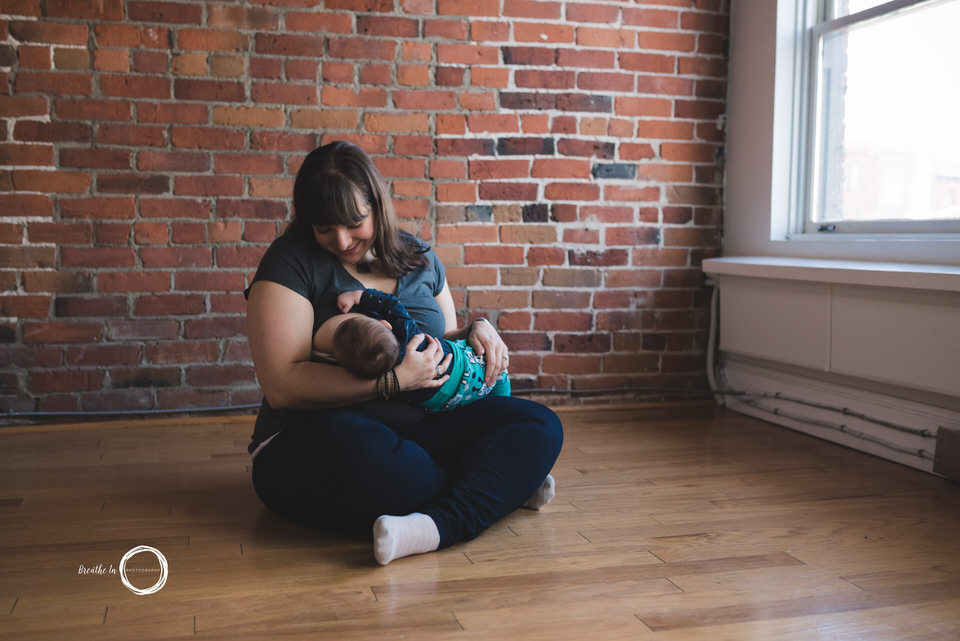 Breastfeeding photo of mom and baby feeding sitting on the floor by a brick wall smiling.