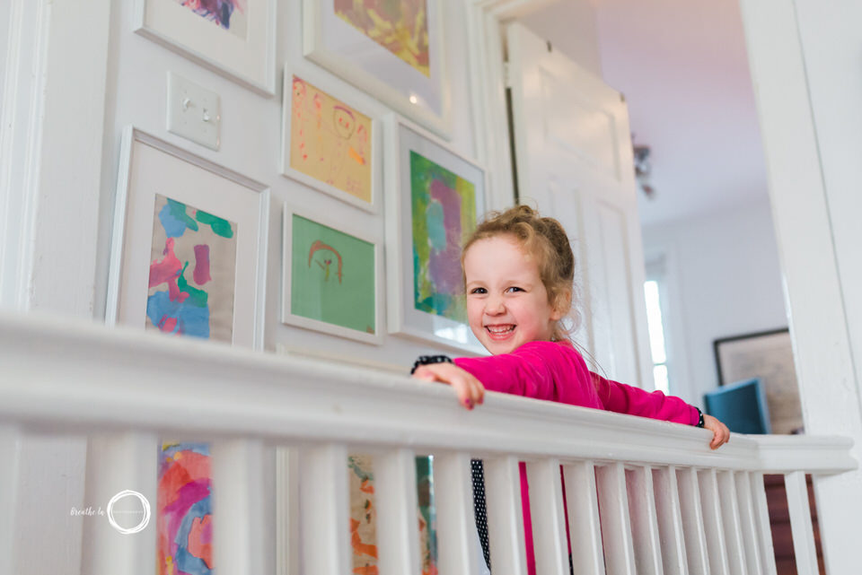 Girl showing me her art wall during home lifestyle photo session.