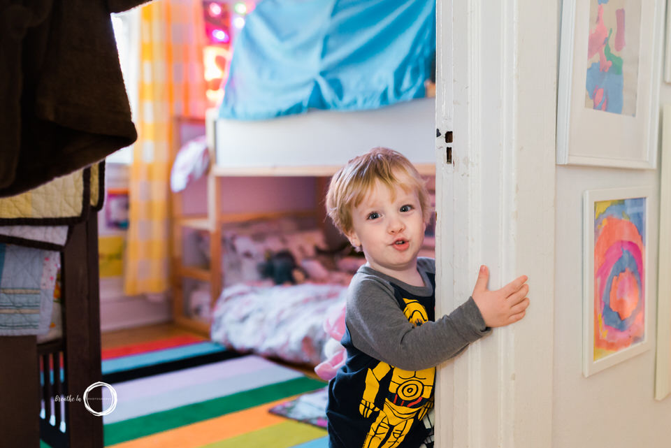 Boy standing by his bedroom door during lifestyle photo session in Ottawa.