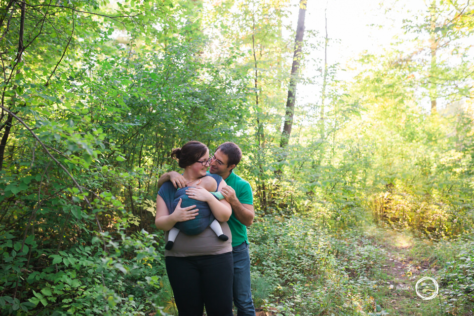 Beautiful mom and dad cuddle baby at Vincent Massey Park.