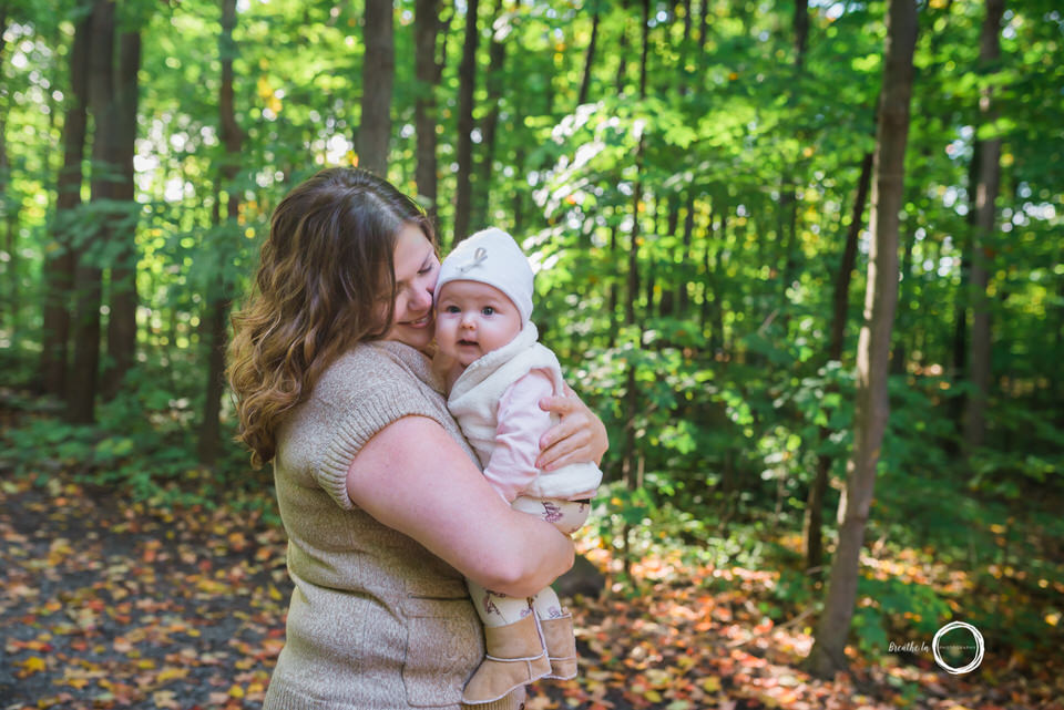 Mom and baby girl cuddling in the forest.